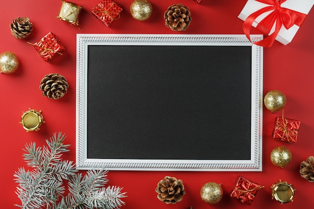Photo frame with free black space around christmas decorations and gifts on a red background. top view, free space for text