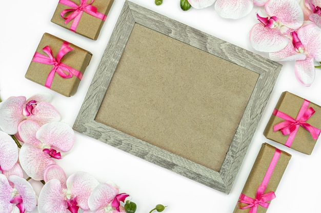 Photo frame with orchid flowers and present or gift boxes