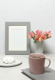 Photo frame with pink flowers, cup coffee, cake on grey table