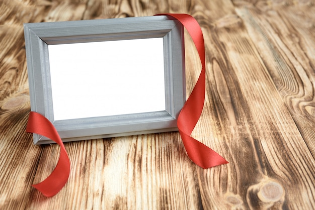 Photo frame with red ribbon on wooden background.