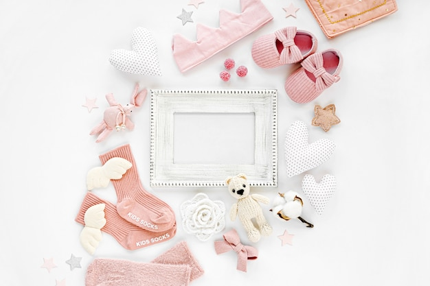 Photo frame with set of clothes and accessories fot newborn girl. toys, socks and baby slippers with hearts on white background. mock up tor text. baby shower concept. flat lay, top view