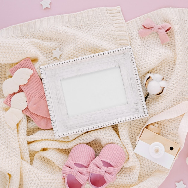 Photo frame with set of clothes and accessories fot newborn. toys, socks and baby slippers with knitted blanket on pink background. baby shower concept. mock up tor text.  flat lay, top view