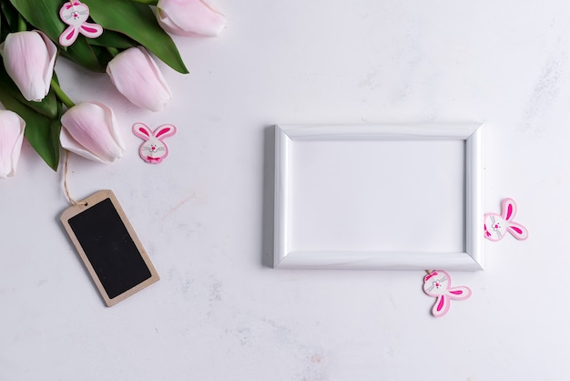 Photo frame with spring tulips with easter bunny on marble table