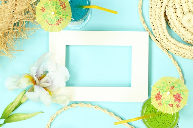 Photo frame with straw bag, flowers and cocktails