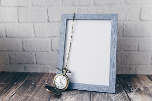 レンガの壁にヴィンテージの丸い時計とフォトフレーム