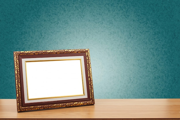 Photo frame on wooden table over green wall background