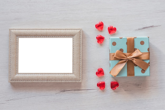 Photo frame on wooden table with gift box, copy space