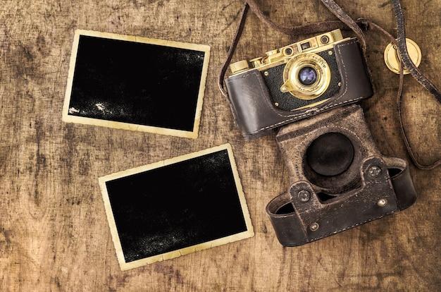 Рамки для фотографий и пленочная камера на деревянном столе. винтажный натюрморт