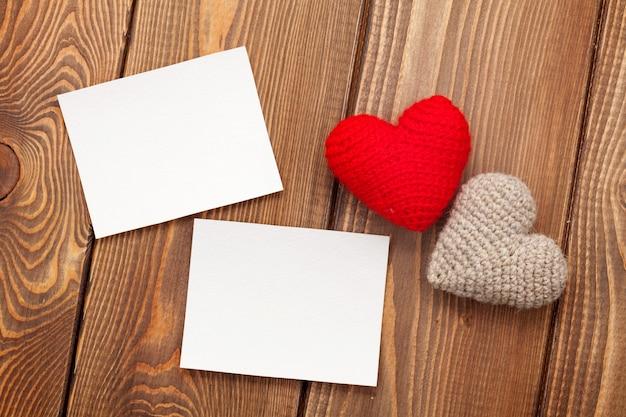 白い木製の背景の上のフォトフレームと手作りのバレンタインデーのおもちゃの心
