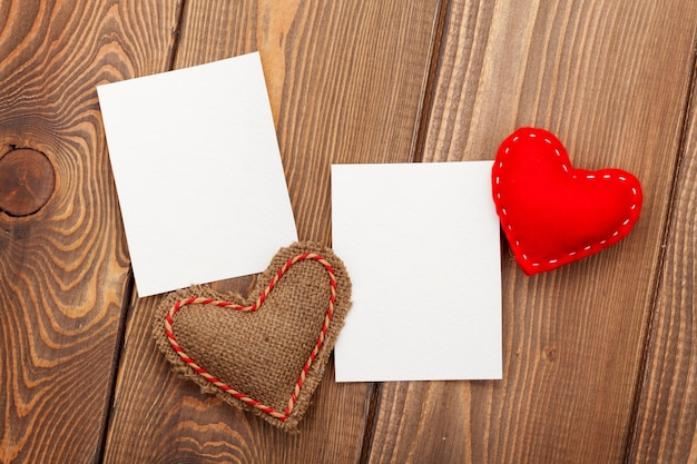木製の背景の上のフォトフレームと手作りのバレンタインデーのおもちゃの心