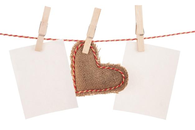 ロープにぶら下がっているフォトフレームとバレンタインデーのおもちゃの心。白い背景で隔離