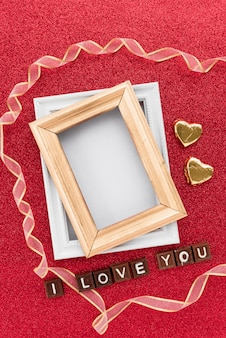Photo frames near ornament hearts, ribbon and i love you inscription