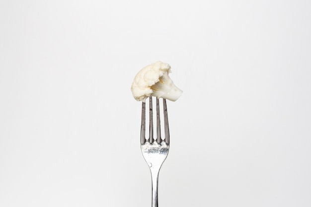 Photo of a fresh cauliflower on a fork isolated on a white background