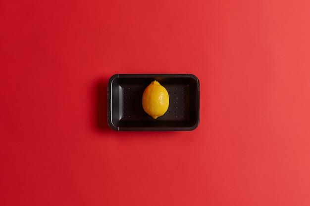 La foto del singolo limone giallo maturo fresco sul vassoio nero ha acquistato nel supermercato isolato sopra fondo rosso. frutta esotica intera contenente molta vitamina c. ingrediente per cucinare la limonata estiva fredda