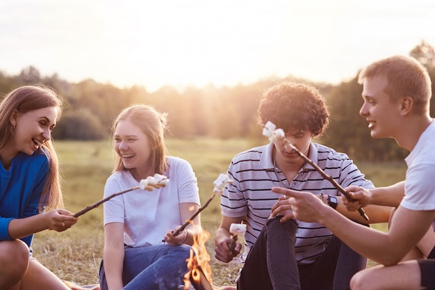 Photo of friendly company of friends have picnic outdoor, roast marshmallows over campfire, have positive expressions, pleasant lively talk, discuss something funny, pose outdoor. friendship