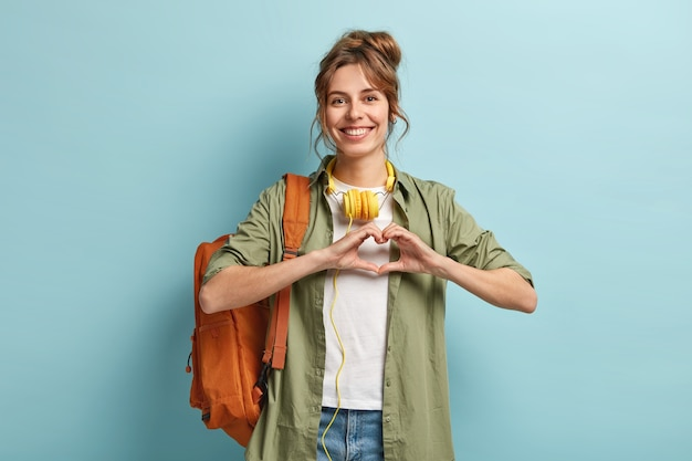 Photo of friendly pretty female traveller makes heart gesture over chest, expresses love to people, travels only with one rucksack