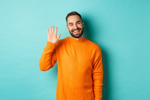 Photo of friendly young man saying hello, smiling and waiving hand, greeting you, standing in orange sweater over light turquoise wall.