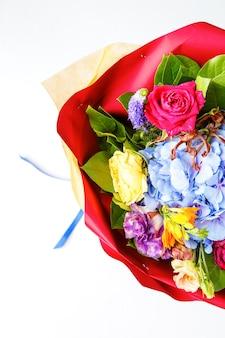 空の白い背景の上のカードとマルチカラーのバラの花束の上からの写真