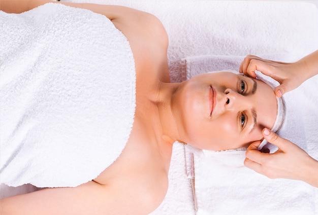 上からの写真。白い布でサロンで年配の女性にヘッドマッサージをしているマッサージ師の手。