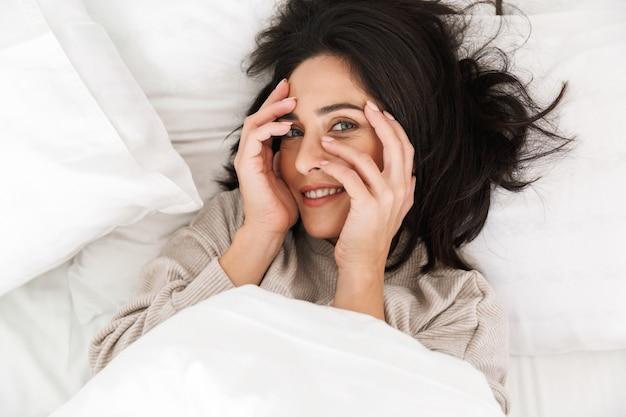 自宅のベッドに横たわっている間笑顔、魅力的な女性30代の上からの写真