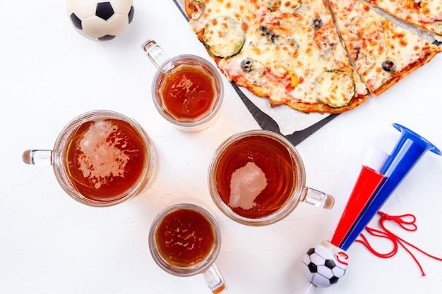 空の白い背景の上の泡ビール、ピザ、パイプとグラスの上からの写真