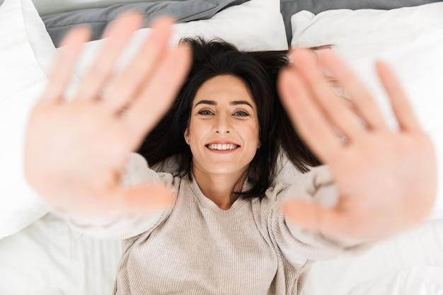 自宅のベッドに横たわっている間笑顔、幸せな女性30代の上からの写真