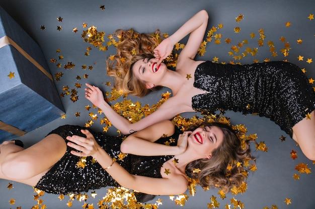 Фотография сверху расслабленной блондинки, лежащей на полу после веселой вечеринки. удивительные девушки дурачатся во время мероприятия, отдыхая на земле с подарками.