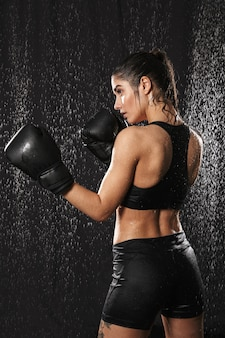 Photo from back of energetic woman boxing wearing gloves and standing in attack position under rain drops, isolated over black background
