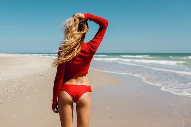 海で見栄えのする完璧な姿の素晴らしい日焼けスリムな金髪の女性の後ろからの写真。赤いビキニを着ています。風の強い髪。トロピカルムード。休日のコンセプトです。
