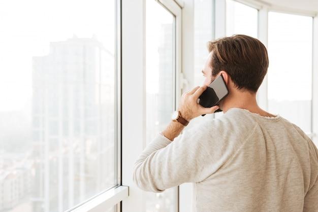 짧은 갈색 머리를 가진 백인 남자의 뒤에서 검은 스마트 폰에서 말하는 동안 창을 통해 찾고 사진