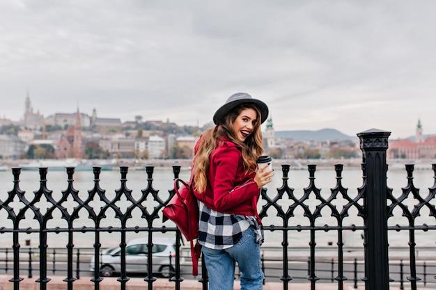 川の景色を楽しむ市松模様のシャツを着た興奮したブルネットの女性の後ろからの写真