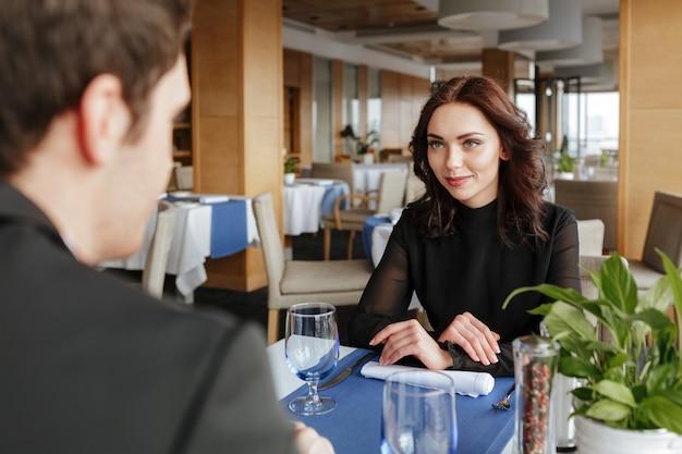 Фото со спины мужчины с женщиной в ресторане