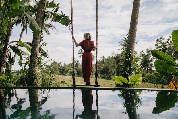 긴 드레스를 입고 슬림 여자 뒤에서 비오는 하늘을보고 사진. 리조트에서 자연 경관을 즐기는 매끈한 여성 모델의 야외 촬영.