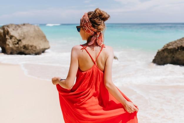 海を見ている日焼けしたゴージャスな女性の後ろからの写真。赤い夏のドレスに立っている素晴らしい白人の女の子の屋外の肖像画。