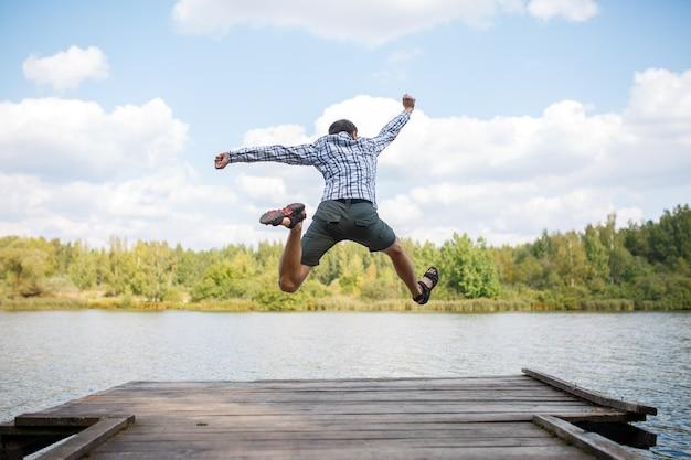 Фотография со спины молодого прыгающего человека на деревянном мосту у реки