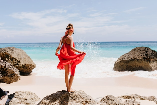 Photo from back of shapely tanned girl standing on big stone. outdoor shot of graceful female model playing with her red dress and looking at ocean waves.