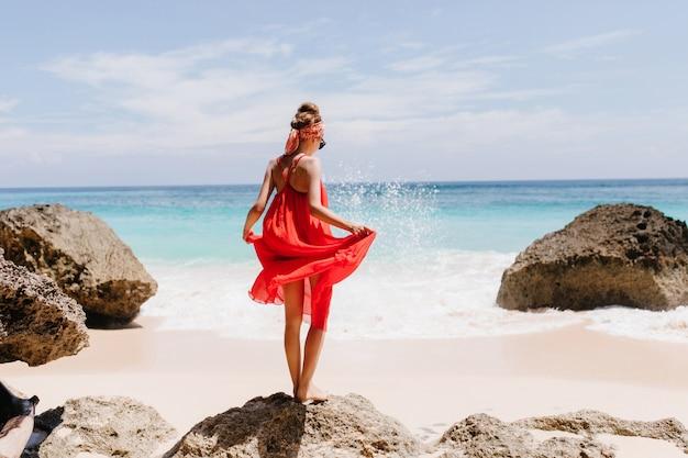Foto dal retro della ragazza abbronzata in piedi sulla grande pietra. colpo esterno del grazioso modello femminile che gioca con il suo vestito rosso e guardando le onde dell'oceano.