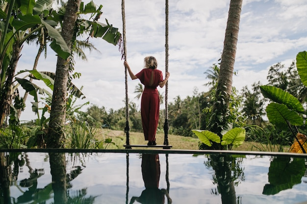 Photo from back of slim woman in long dress looking at rainy sky. outdoor shot of shapely female model enjoying nature views at resort.