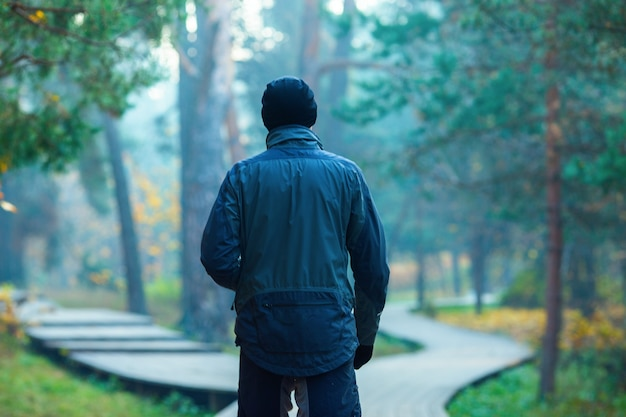 Photo from back of standing athlete in autumn park