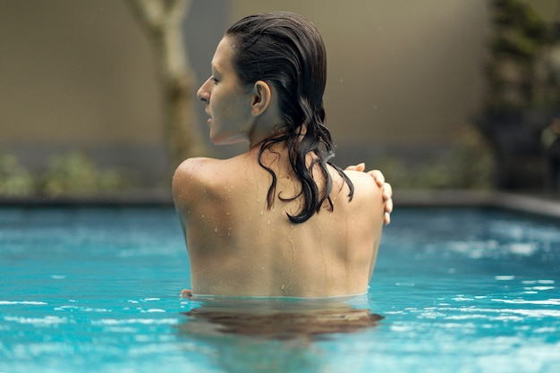 Photo from the back of a wet girl in the pool.
