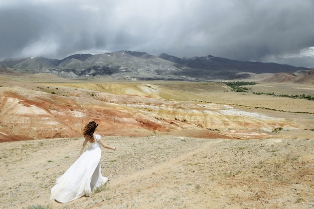 Photo from the back a woman-bride in a wedding dress walks confidently across the desert mountains with a beautiful view. honeymoon travel concept