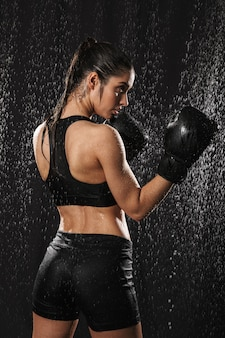 Photo from back of workout woman boxing wearing gloves and standing in attack position under water drops, isolated over black background