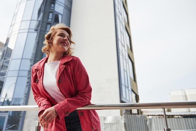 Фото снизу. взрослая красивая женщина в теплом красном пальто прогуливается по городу в выходные дни