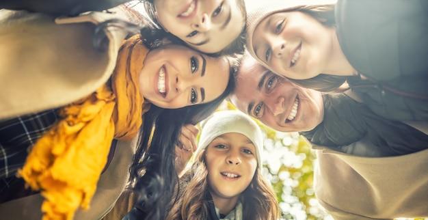 На фото снизу изображена счастливая семья с тремя детьми, улыбающимися и складывающими головы.