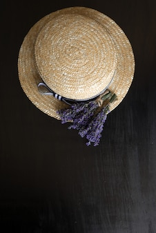 Photo from above on black wood is a brown hat with dried flowers of provencal herbs. top view
