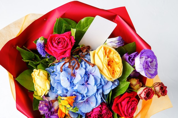 Photo from above bouquet of multi-colored roses with card on empty white background