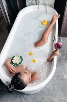 Photo from above: girl posing while lying in a foam bath, with a flower and ducks, with a glass of red wine in her hand, enjoying relaxation. enjoyment. personal care.