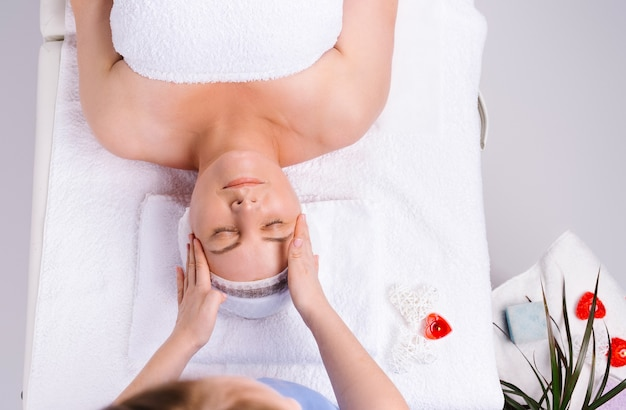Photo from above. hands of female masseur giving head massage to senior woman in salon with scented
