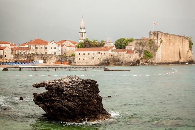高い石壁と塔のある美しい古い海辺の街ブドヴァの海からの写真