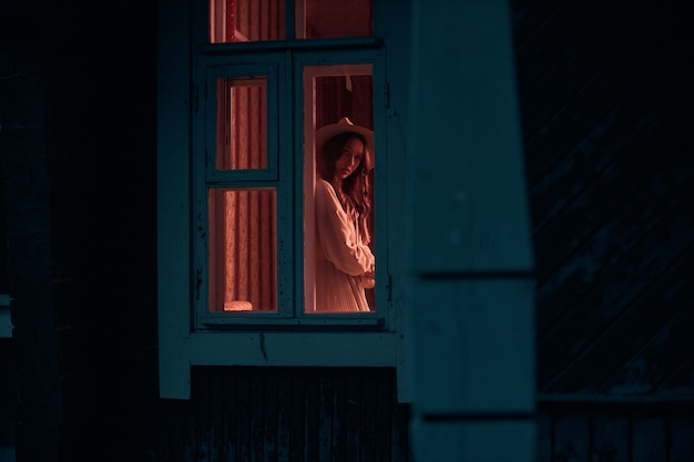 Photo from the street to the mysterious girl who stands in the window in a room with the lights on creative photography high quality photo